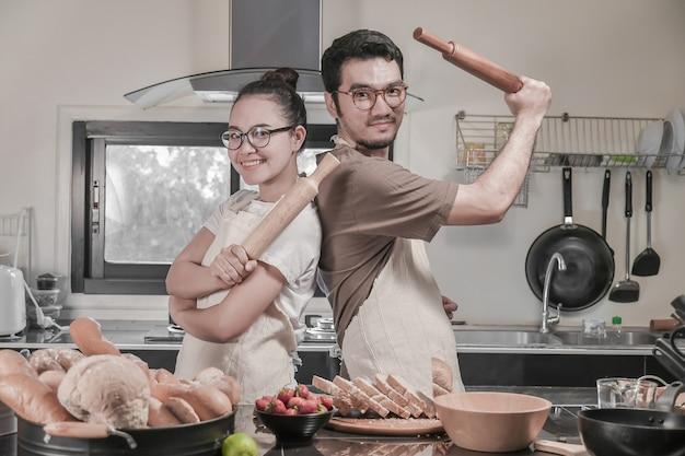 Glückliche junge paare, die in der küche, asiatische paartätigkeit in der küche kochen. Premium Fotos