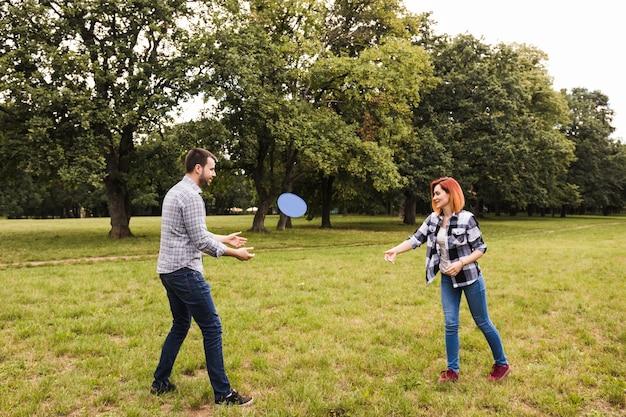 Glückliche junge paare, die mit fliegendiskette im garten spielen Kostenlose Fotos