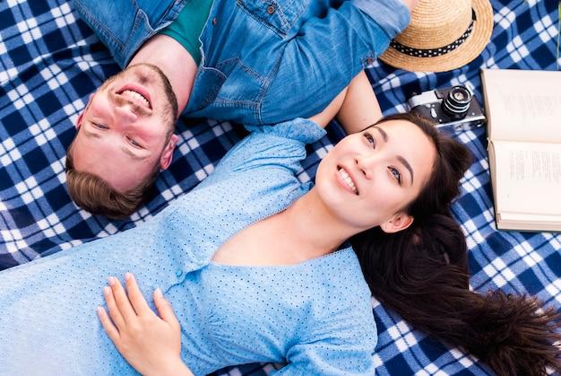 Glückliche junge paare, die rest auf decke genießen Kostenlose Fotos
