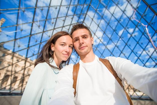Glückliche junge paare, die selfie in paris auf europäischen ferien nehmen Premium Fotos