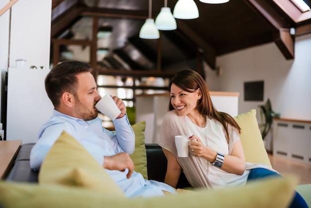 Glückliche junge paare, die spaß auf dem sofa haben Premium Fotos