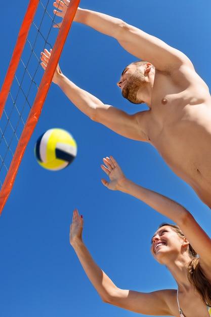 Glückliche junge paare, die volleyball spielen Premium Fotos