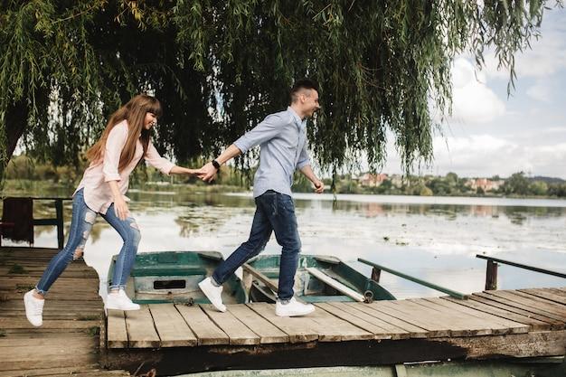 Glückliche junge paare draußen. junge liebespaare, die händchenhalten einer holzbrücke laufen lassen. Premium Fotos