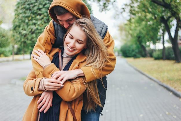 Glückliche junge paare in den liebesjugendlichfreunden kleideten in der zufälligen art an, die zusammen auf herbststadtstraße sitzt Premium Fotos