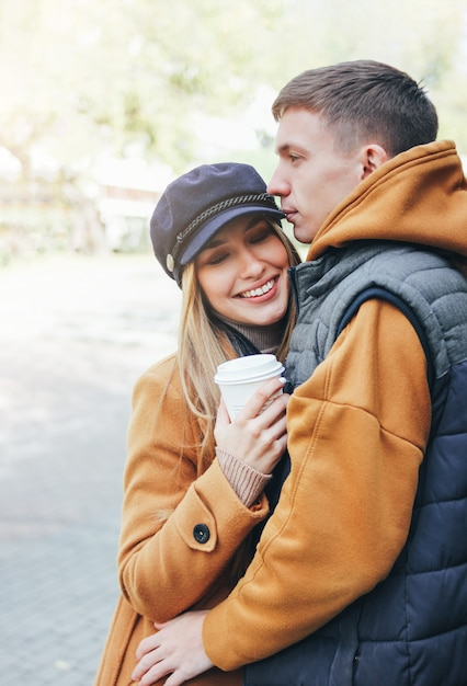 Glückliche junge paare in den liebesjugendlichfreunden kleideten in der zufälligen art an, die zusammen auf stadtstraße in der kalten jahreszeit geht Premium Fotos