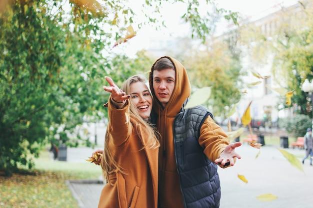 Glückliche junge paare in den liebesjugendlichfreunden kleideten in der zufälligen art an, die zusammen geht und wirft blätter an der kamera, herbststadtstraße Premium Fotos