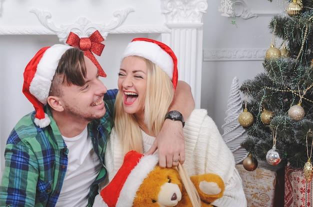 Glückliche junge paare in der cacsual kleidung und in den lustigen hüten, die weihnachten feiern Premium Fotos