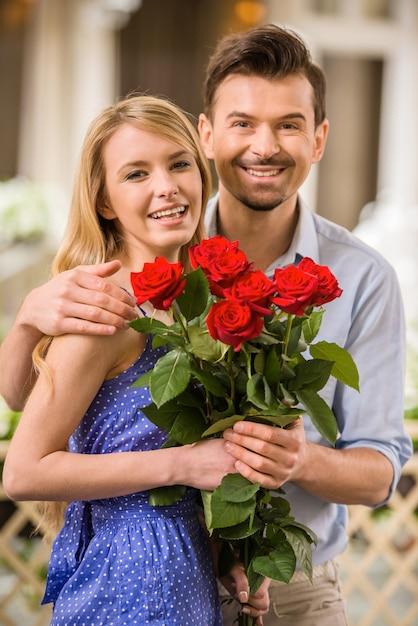 Glückliche junge paare mit rosenblumenstrauß auf einem datum. Premium Fotos