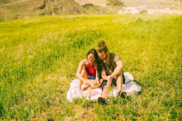 Glückliche junge paare unter verwendung der tablette in der lichtung Kostenlose Fotos