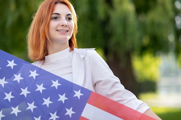 Glückliche junge rothaarige frau, die mit usa-nationalflagge steht, die draußen im sommerpark steht. positives mädchen, das unabhängigkeitstag der vereinigten staaten feiert. konzept des internationalen tages der demokratie. Premium Fotos