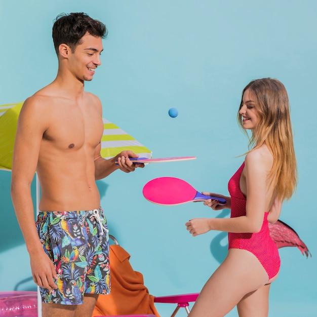 Glückliche junge schatze in der strandkleidung, die tischtennis im studio spielt Kostenlose Fotos