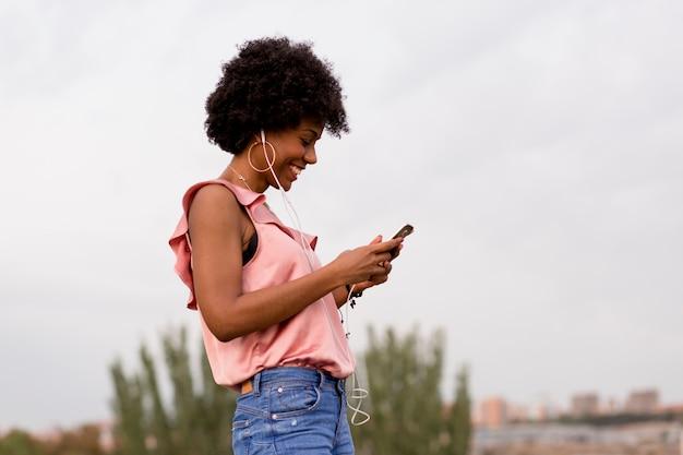Glückliche junge schöne afroamerikanische frau, die musik auf ihrem handy hört und lächelt. städtischer hintergrund. frühlings- oder sommersaison. legere kleidung. Premium Fotos