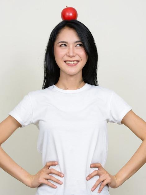 Glückliche junge schöne asiatische frau, die mit apfel auf kopf denkt Premium Fotos
