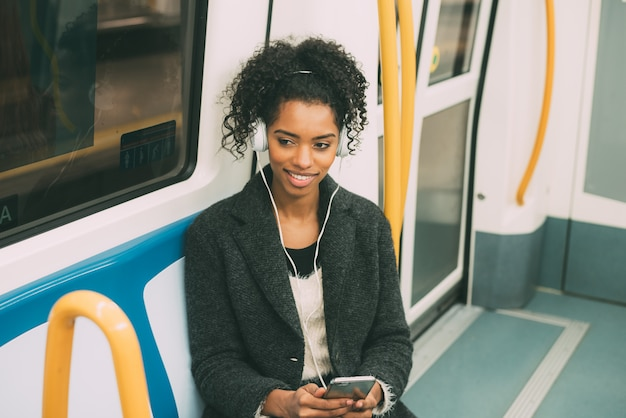 Glückliche junge schwarze frau, die innerhalb des untergrunds hört musik sitzt Premium Fotos