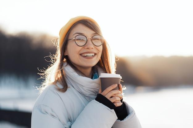 Glückliche junge teenagerfrau, die eine kaffeetasse zum mitnehmen hält Kostenlose Fotos