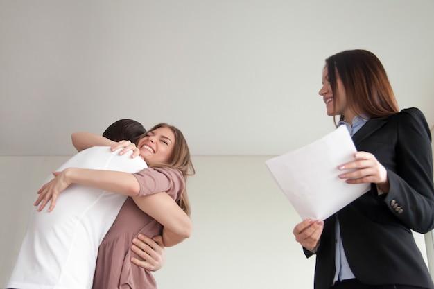 Glückliche junge umarmende familienpaare, kauften gerade neues apartmenthaus Kostenlose Fotos