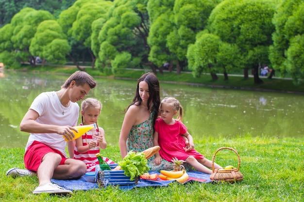 Glückliche junge vierköpfige familie, die nahe dem see picknickt Premium Fotos