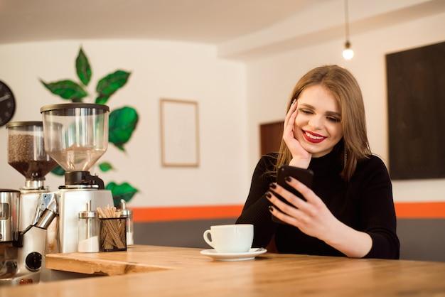 Glückliche kaukasische frau, die ihr foto am zelltelefon bei der entspannung im café aufpasst. Premium Fotos