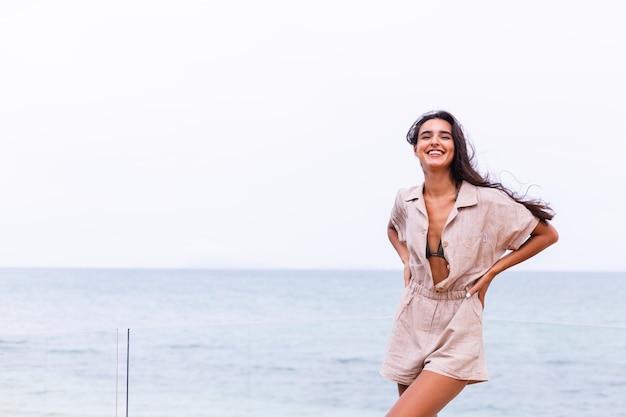 Glückliche kaukasische frau im beige stilvollen trebdy overall am windigen bewölkten tag im strand Kostenlose Fotos