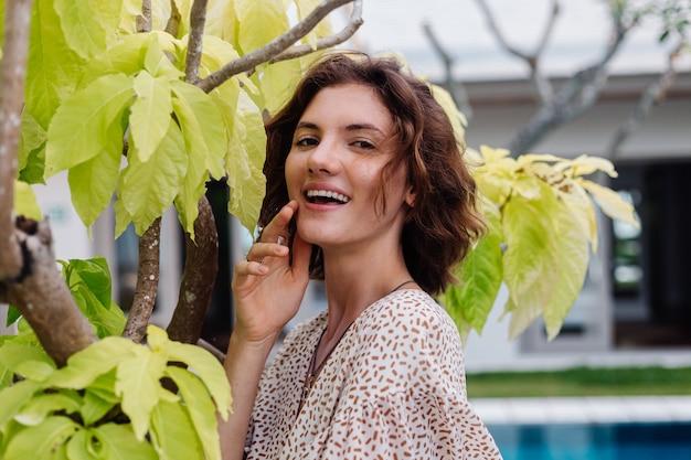 Glückliche kaukasische frau im kurzen sommerkleid außerhalb des villenhotels durch baum und blauen swimmingpool Kostenlose Fotos