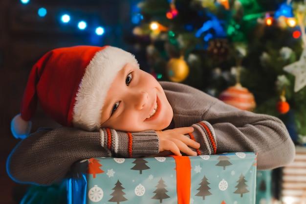 Glückliche kinder des kleinen jungen in sankt-hut mit geschenk haben weihnachten oder neues jahr. Premium Fotos