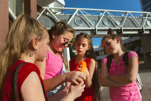 Glückliche kinder, die an der straße der stadt am sonnigen sommertag vor dem modernen gebäude spielen. gruppe von glücklichen kindern oder jugendlichen, die spaß zusammen haben. konzept der freundschaft, kindheit, sommer, ferien. Kostenlose Fotos