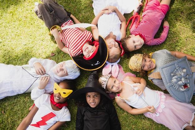 Glückliche kinder, die auf dem gras liegen Premium Fotos