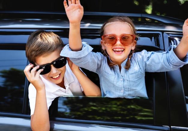 Glückliche kinder, die heraus das autofenster schauen Premium Fotos