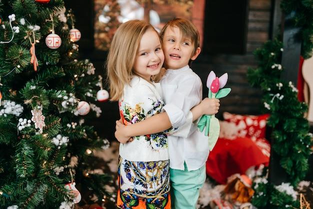 Glückliche kinder, die im studio mit dekorationen des weihnachtsbaums und des neuen jahres umarmen. Premium Fotos