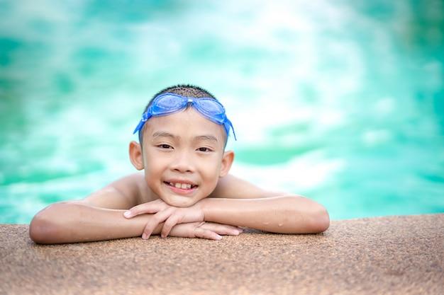 Glückliche kinder, die im swimmingpool spielen und schwimmen Premium Fotos