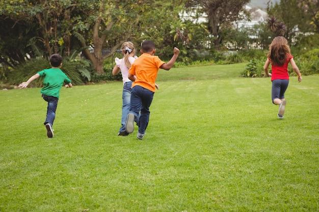 Glückliche kinder, die über das gras laufen Premium Fotos