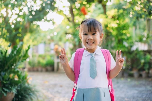 Glückliche kinder im studentenanzug und in der tasche bereit, zum lernen zur schule zu gehen Premium Fotos