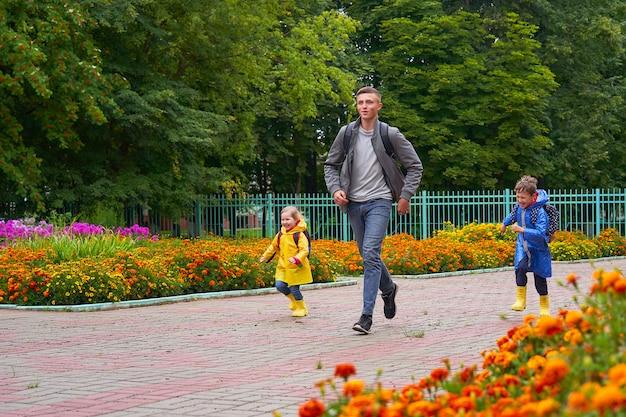 Glückliche kinder lachen in eile und laufen in regenmänteln mit einer aktentasche hinter einem rucksack zur schule. Premium Fotos