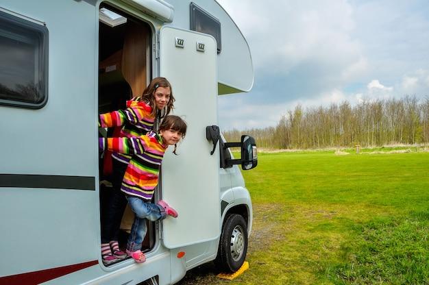Glückliche kinder nähern sich dem wohnmobil (rv), das spaß, familienurlaubreise im wohnmobil hat Premium Fotos