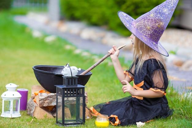 Glückliche kleine hexe haben spaß draußen an halloween. süßes oder saures. Premium Fotos