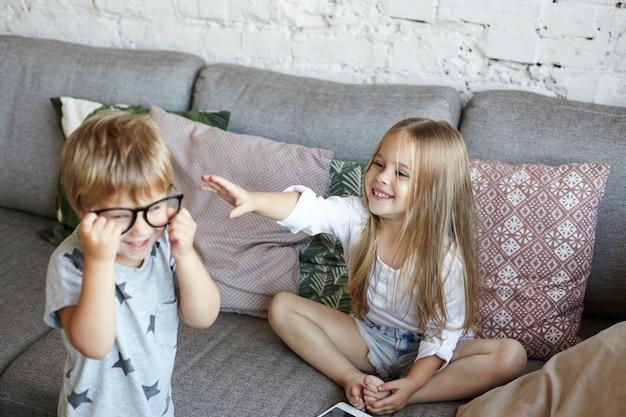 Glückliche kleine kinder spielen im wohnzimmer Kostenlose Fotos