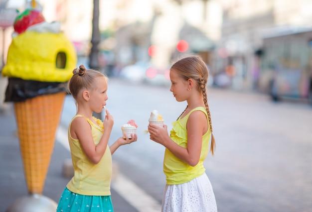Glückliche kleine mädchen, die eiscreme-freiluftcafé essen. menschen, kinder, freunde und freundschaftskonzept Premium Fotos