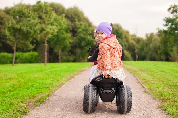 Glückliche kleine süße mädchen fahren draußen ein motorrad Premium Fotos