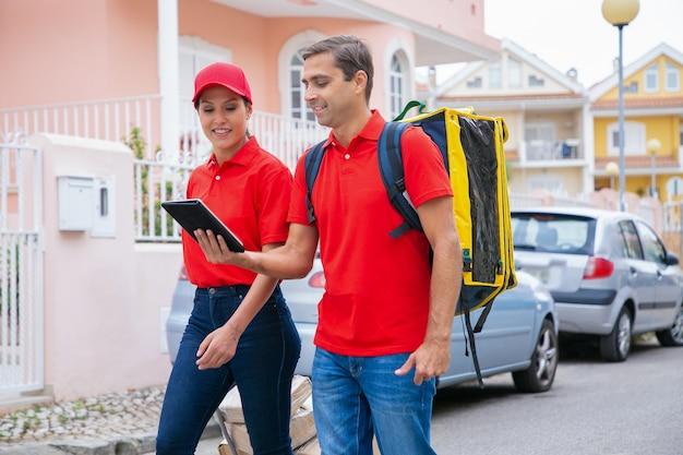 Glückliche kuriere liefern bestellung, arbeiten im expressdienst und tragen rote mütze und hemd. lieferbote, der gelben rucksack trägt und tablette hält. lieferservice und online-shopping-konzept Kostenlose Fotos