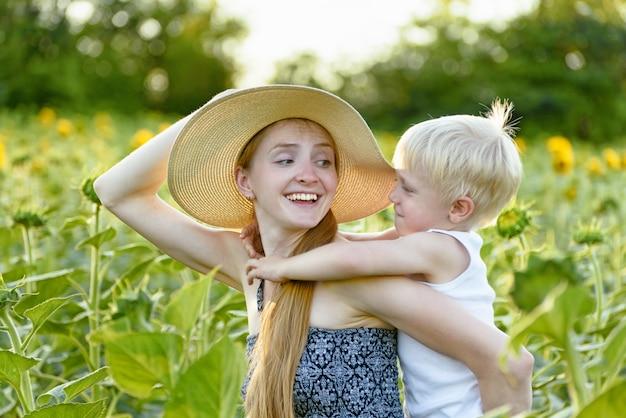 Glückliche lachende mutter, die kleinkindsohndoppelpolfahrt auf grünes blühendes sonnenblumenfeld gibt Premium Fotos