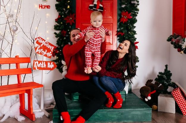 Glückliche lächelnde familie am studio auf hintergrund des weihnachtsbaums mit geschenk Kostenlose Fotos