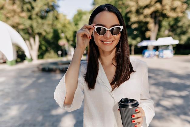 Glückliche lächelnde frau, die weißes hemd und weiße gläser trägt, die kaffee draußen an gutem sonnigen tag im stadtpark trinken Kostenlose Fotos