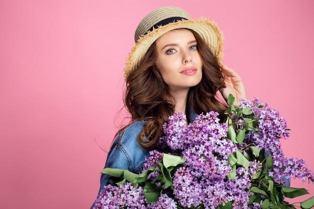 Glückliche lächelnde frau im strohhut, der mit blumenstrauß der lila blumen aufwirft Premium Fotos