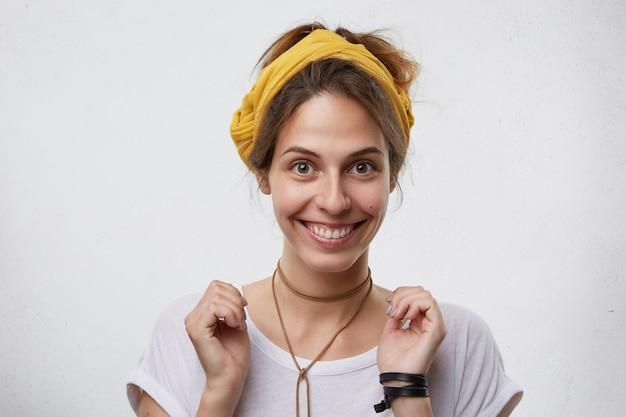 Glückliche lächelnde frau mit braunen augen, die beiläufig im weißen t-shirt und im gelben stirnband gekleidet sind. freudige attraktive hausfrau, die sich freut, ihre verwandten zu sehen. menschen, emotionen Kostenlose Fotos