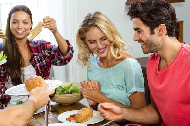 Glückliche lächelnde freunde beim zu mittag essen Premium Fotos