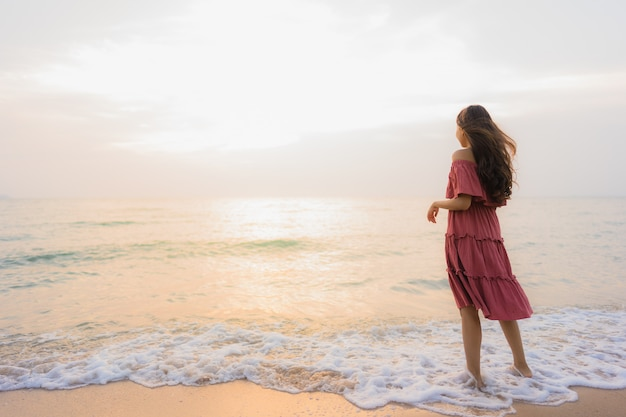 Glückliche lächelnfreizeit der schönen jungen asiatischen frau des porträts auf dem strandmeer und -ozean Kostenlose Fotos