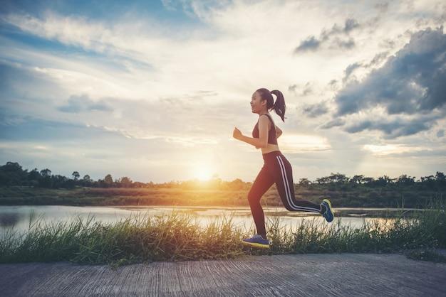 Glückliche läuferfrau läuft in der rüttelnden übung des parks. Kostenlose Fotos