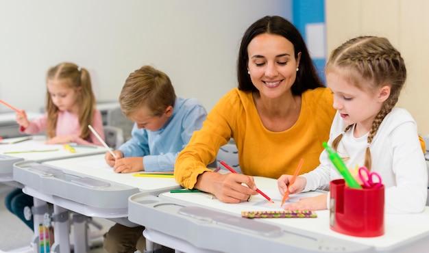 Glückliche lehrerin, die ihren schülern hilft Kostenlose Fotos