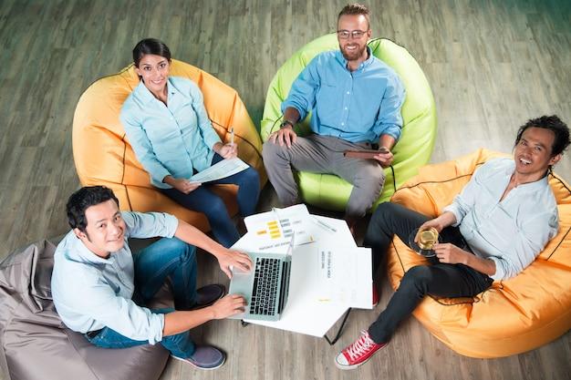 Glückliche leute sitzen auf sitzsack stühle um tisch Kostenlose Fotos