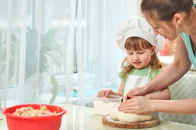 Glückliche liebende familie, die bäckerei zusammen vorbereitet. mutter lehrt kind, wie man kocht Premium Fotos